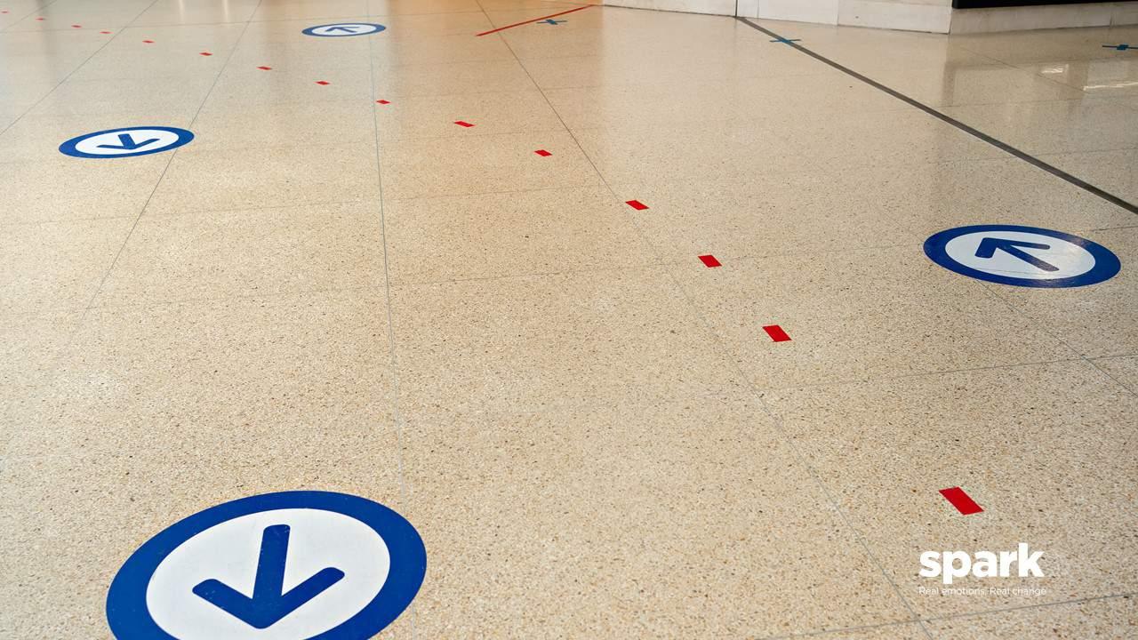 Floor sticker social distancing arrows in UK supermarket Tesco COVID