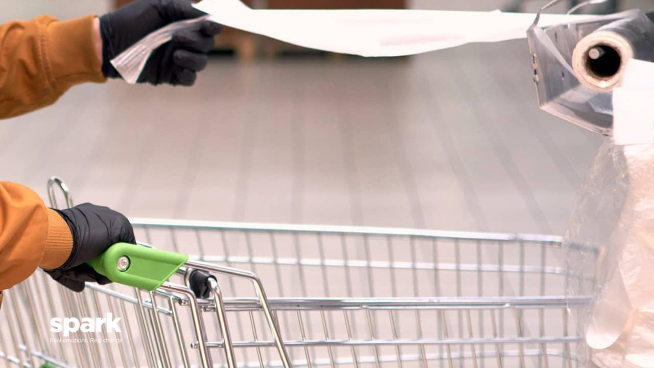 Shopper cleaning trolly in store COVID