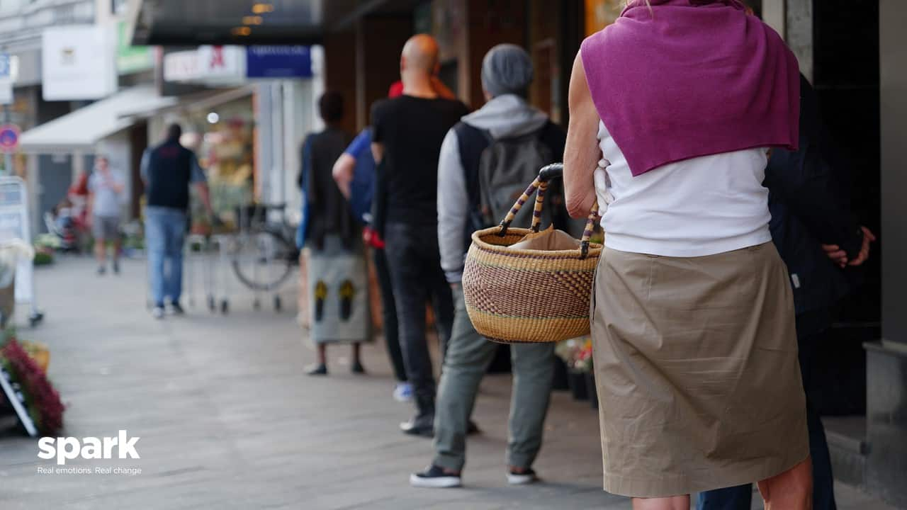 Shoppers queing outside supermarket COVID